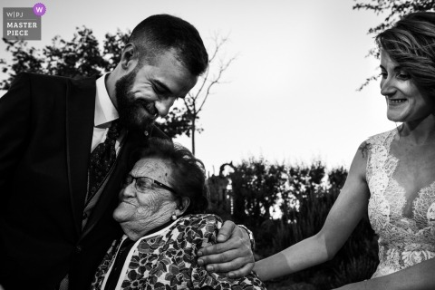 Seseña, Toledo documentary wedding photo of a groom hugging an elderly woman as his bride also embraces her