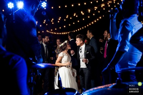 Torrelodones, sesión de boda en Madrid con una pareja enmarcada a través de los músicos con instrumentos en la fiesta de recepción