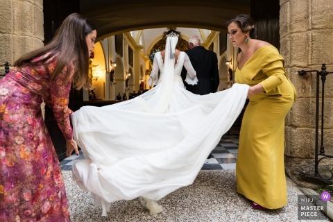 Kadyks, Andaluzja zdjęcie ślubne druhny ustalające pociąg sukienkę przed kościołem | fotografia ślubna do Madrytu