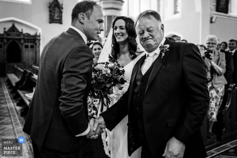 Meath, Ireland wedding photograph of the father of the bride shaking hands with the groom at the ceremony altar.