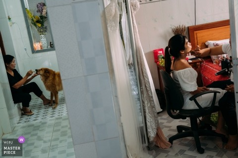 Documentary wedding photography at Ho Chi Minh of the bride having her makeup applied