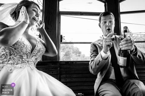Huwelijksshoot met New Jersey-bruidegom die een champagnefles knalt terwijl zijn nieuwe bruid reageert