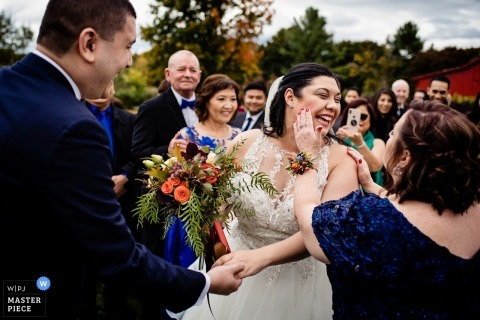 Picture of a bride having lipstick wiped off her cheek by a top Charlotte, Vermont wedding photographer