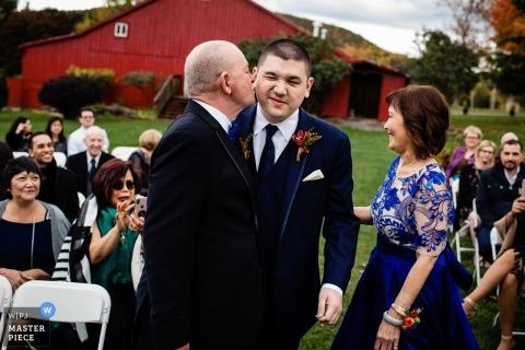 Dokumentalna fotografia ślubna pana młodego, który całuje się w policzek od ojca w ceremonii plenerowej w Charlotte, Vermont w pobliżu czerwonej stodoły