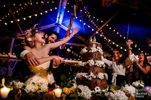 Wedding shoot with Putney, Vermont couple as they cut their cake before cheering guests