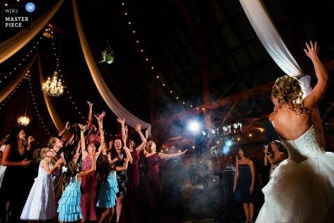 Kalifornijska dokumentalna fotografia ślubna panny młodej rzucającej jej bukiet dla gości na parkiecie