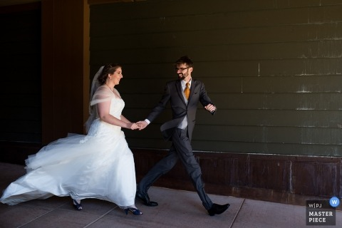 Truckee, CA wedding shoot with a couple quickly walking Down the sidewalk