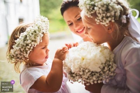 Podcetrtek, Słowenia Ślubna fotografia Flowergirls sprawdzających bukiet ślubny z panną młodą