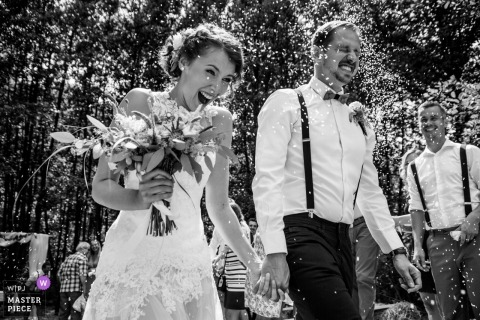 Picture of a couple laughing and reacting to flying confetti by a top Prague wedding photographer
