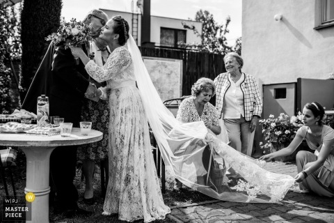 Wedding pictures by Prague photographer showing the bride kissing her fatherg the ceremony as Family and bridesmaids fix her veil train durin