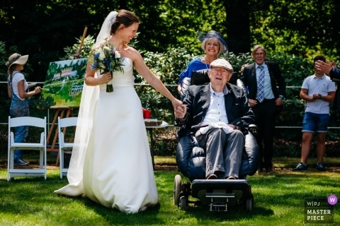 Wedding photojournalism at Arnhem of a bride holding her bouquet and the hand of a man in a wheelchair