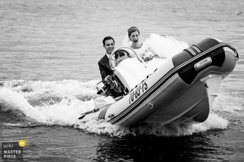 Aalst, Gelderland, Nederland ślubna fotografia panny młodej i pana młodego przybywających małą łódką na jeziorze.