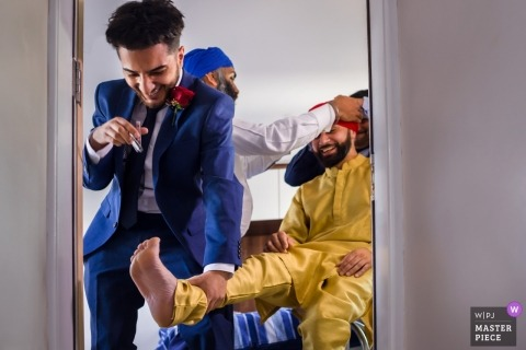 Wedding pictures of the groom getting help into his ceremony clothing - London photographer