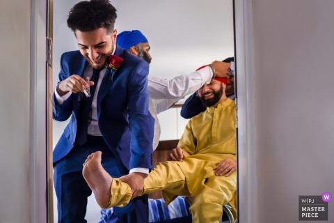 Hochzeitsfotos des Bräutigams, die Hilfe in seine Zeremoniekleidung bekommen - London-Fotograf