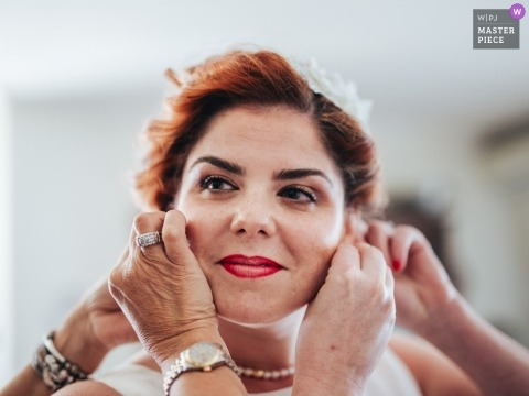 Fotoreportaż ślubny Obraz z Porto panny młodej, która otrzymuje pomoc, wkładając kolczyki