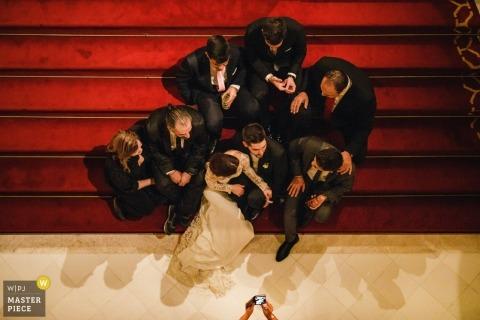Ślubny krótkopęd z Porto parą siedzi na czerwieni wykłada dywanami z przyjaciółmi dla portreta po ceremonii
