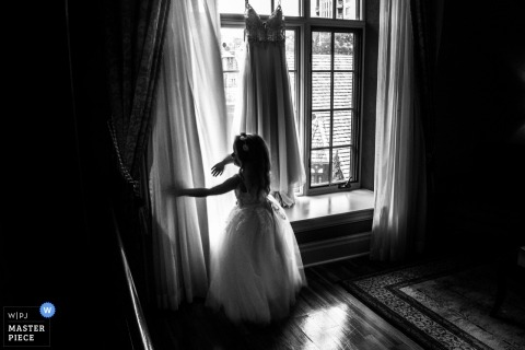 OLD MILLS TORONTO wedding photograph of flower girl playing with bride's gown hanging by curtains in the window.