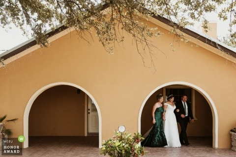 Documentary wedding photograph of a bride and her parents exiting an arched building at Mission, Texas