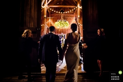 Lenox, Massachusetts Wedding Photograph of bride and groom entering their barn reception party