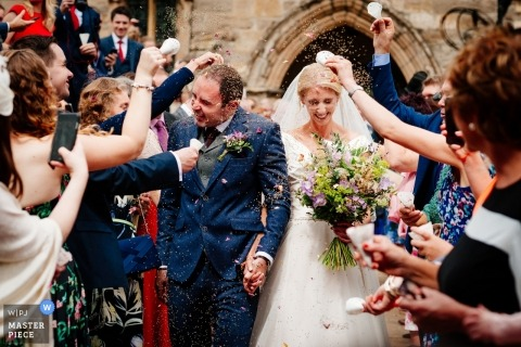 East Bridgford Hill Wedding Photograph of Bride and Groom leaving church under flower petals tossed by guests