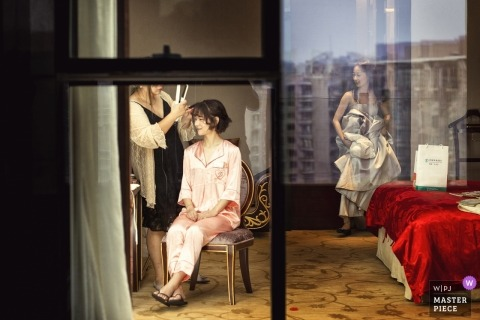 Wedding photo shoot in Henan China what's the bride having hair preparations performed in a room with the city reflected in the Glass windows
