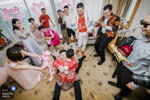 Zhengzhou, Henan ślubny fotoreportaż przedstawiający dwóch drużbów grających w brudne gry drzwiowe w Chinach
