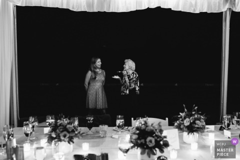 A young woman and old woman talking with cake at a reception | NY wedding | Tete-a-Tete