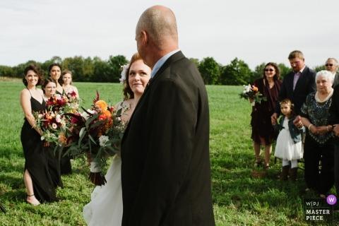 Oblubienica patrzy na swojego ojca, gdy idzie po alejce podczas ceremonii ślubnej | Oczy miłości i dzięki