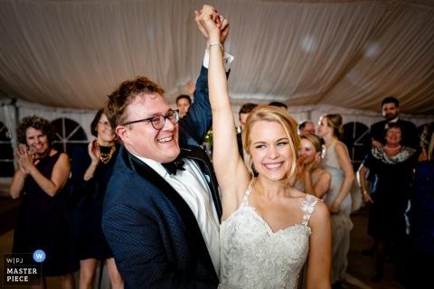 Zdjęcie ślubne młodej panny młodej i pana młodego z Oatlands w stanie Leesburg, podnoszących ręce na parkiecie tanecznym pod namiotem.