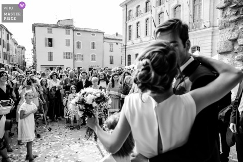 Wedding shoot with France couple kissing on the streets as she holds her bouquet before a large number of guests