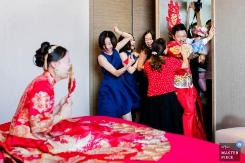 Fujian wedding photograph of the groom gatecrashing past the women to get to his new bride