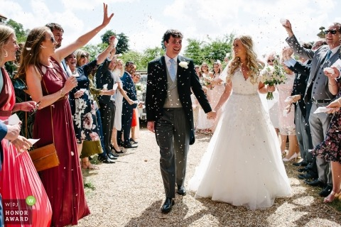 Stansted Park, Hampshire, UK Wedding Ceremony | Bride and Groom pass under shower of confetti at their outdoor wedding