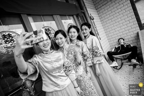 Dokumentalna fotografia ślubna w Fujianie przedstawiająca cztery kobiety w kolejce do zdjęcia selfie, podczas gdy mężczyzna śpi na krześle za nimi