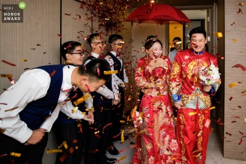 Fujian wedding photojournalism image of a couple dressed in red with a red umbrella as confetti flies