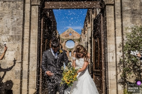 Italy Wedding Photographer captured bride and groom under confetti sky - San Galgano Abbey, Siena