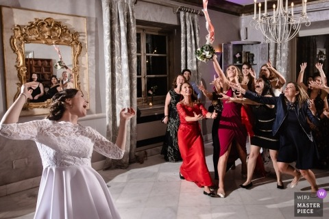 Toledo documentary wedding photo of the bride tossing her bouquet to the single ladies - strobed wedding reception lighting