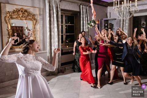 Toledo dokumentalna fotografia ślubna panny młodej podrzucającej bukiet do samotnych pań - oślepione oświetlenie wesela