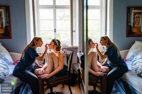 Hesse photo de mariage d'une femme maquillant la mariée se reflétant dans un mur de verre | Photographie de mariage en Allemagne