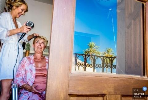 Panna młoda i mama naprawiają włosy w domu przed ślubem.