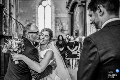 Les Andelys wedding photos of a bride receiving a kiss from her father inside the church