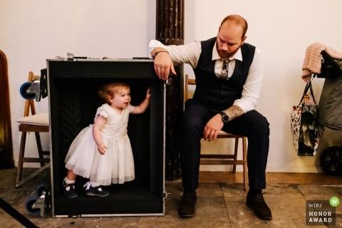 De huwelijksfoto van Londen van een jong bloemenmeisje kleedde zich omhoog en speelde binnen een musicusversnellingsbak bij de ontvangst