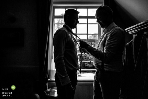 Kasteel De Wittenburg, Wassenaar, Netherlands wedding image of the Best man putting on tie with groom