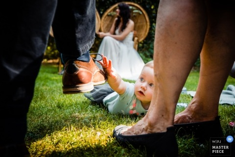 Utrecht documentary wedding photo of a baby crawling in the grass during the outdoor wedding ceremony