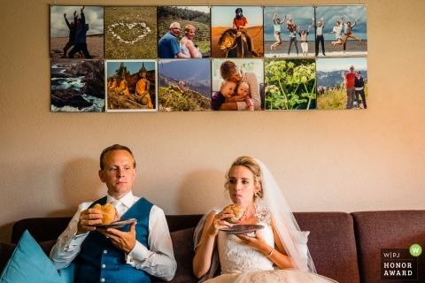 Utrecht-Hochzeitsfotojournalismusbild eines Paares, das auf einer Couch hat eine schnelle Mahlzeit sitzt