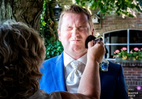 Delft - Netherlands groom has powder applied to cheeks before ceremony