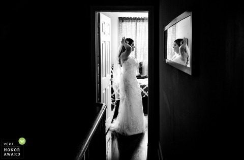 Toronto, Canada bride preparing her hair in mirror - reflecting in wall hanging glass