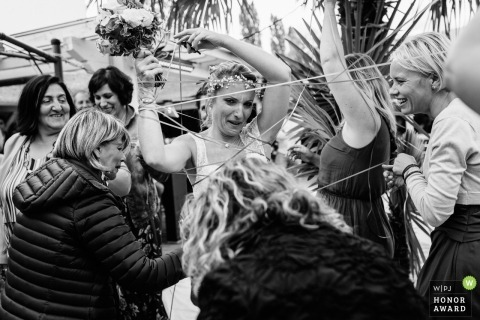 Auvergne-Rhône-Alpes documentary wedding photo of a bride tangled in string as her friends help to free her