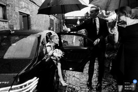London wedding photo of the bride getting out of the car in the rain covered with umbrellas | wedding photography in black-and-white