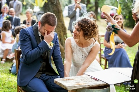 Viareggio wedding photojournalism image of a groom overcome with emotion during his outdoor ceremony under the trees