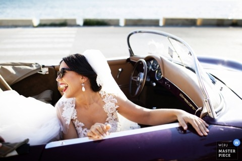 Wedding picture of a bride in the passenger seat of a purple convertible auto looking back and laughing - Marsala, Sicilia photographer